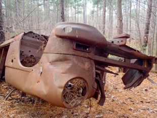 A flipped car, circa 1950, sits trailside as a reminder of the area's past.